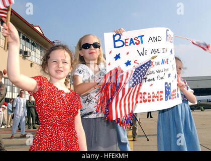 030528-N-8327M-004 Naval Station Norfolk, Va. (May 28, 2003) -- Lt. Cmdr. Andrew BurdenÕs family members wave flags - Stock Photo