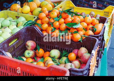 Fruit overflowing boxes on the counter of the local market, tangerines, oranges, apples. - Stock Photo