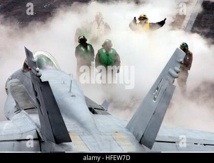 040225-N-9907G-005 Onboard USS Harry S Truman (CVN 75). Through dense steam, a plane director guides a FA-18C from - Stock Photo