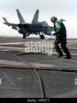 040325-N-6213R-128  Pacific Ocean (Mar. 25, 2004) - An Aviation Boatswain's Mate keeps the arresting cable on track - Stock Photo