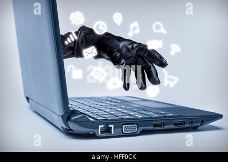 A gloved hand reaching out through a laptop with common media icons flowing, signifying a cybercrime or Internet - Stock Photo
