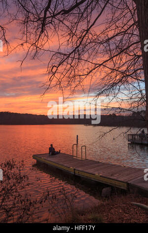 Lonely girl sitting on the pier in lake raleigh during sunset. - Stock Photo
