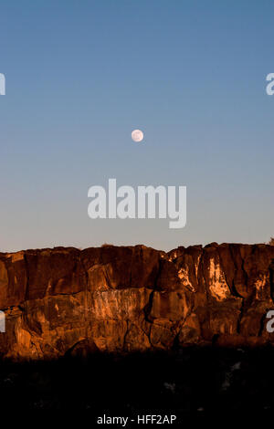 Moonrise over the cliffs in Petroglyph National Monument, Albuquerque, New Mexico in a vertical photo - Stock Photo
