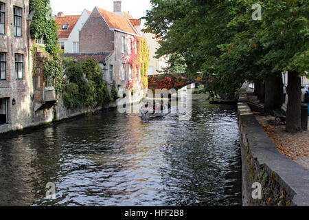 The canals of Bruges offer charm and a unique vantage to view the city, and tour boats ply their way through the - Stock Photo