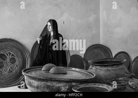 young woman in  traditional dress (abaya) in Jabreen Castle in Oman - Stock Photo
