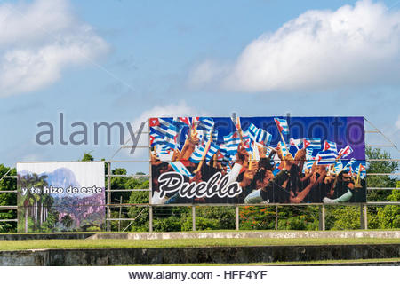 Two Revolutionary billboards in Che Guevara square. Behind it are groups of trees and the blue sky. - Stock Photo