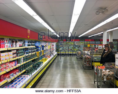No Frills: Grocery items displayed on racks til far end in a Canadian grocery store. Iron basket stands on the opposite - Stock Photo