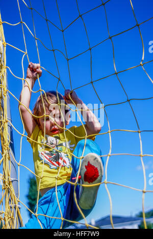 Young boy plays on schoolyard recreational equipment. - Stock Photo
