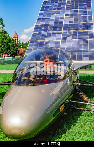 A young boy sits in the cockpit of a solar powered car on display at a solar technology show. - Stock Photo