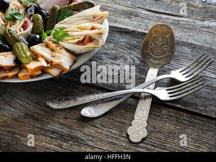 Plate of cold meats with ham, bacon, olives and pickles - Stock Photo