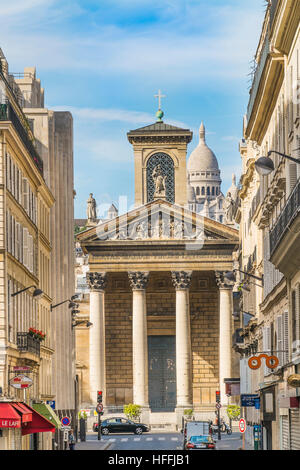 view from rue lafitte towards south facade of notre dame de lorette, sacre coeur basilica in the background - Stock Photo