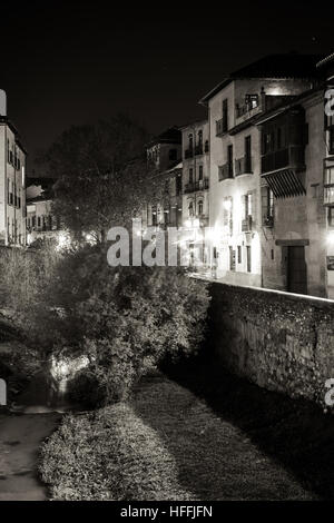 Urban scene of a river crossing the old part of the city of Granada, Spain, taken at night - Stock Photo