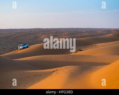 Off-road vehicle on sand dunes, evening light, desert, Sharqiya Sands or Wahiba Sands, Al Raka, Oman - Stock Photo