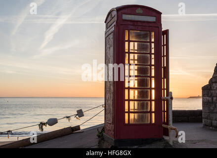 bright red telephone box on beach front at sunrise - Stock Photo