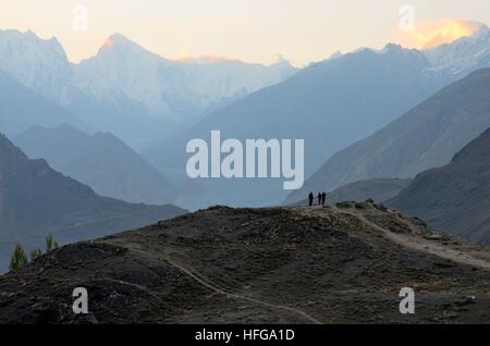 Men on mountain peak watch sunrise among the Karakoram mountains in Duiker Plateau Hunza Valley Pakistan - Stock Photo