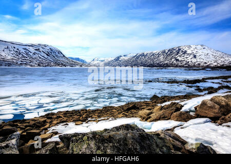 The ice breaking up on the lake in Fjordane, Norway in Spring. Isolated pockets of ice remain on the land. - Stock Photo