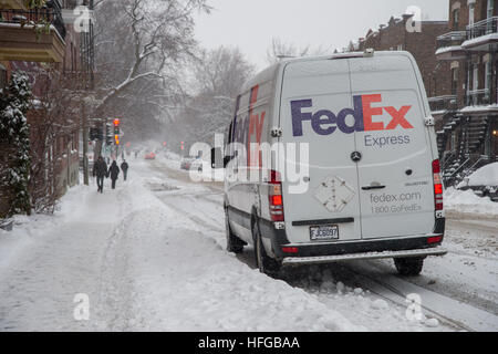 Montreal, CA - 12 December 2016: A FedEx truck is parked on Laurier Street during snow storm. - Stock Photo