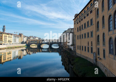 View of Arno river embankment with architecture and Ponte Vecchio bridge reflected on water - Stock Photo