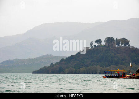 Boat on dock at Khanpur dam, Pakistan with clouds green mountain range in the background. - Stock Photo