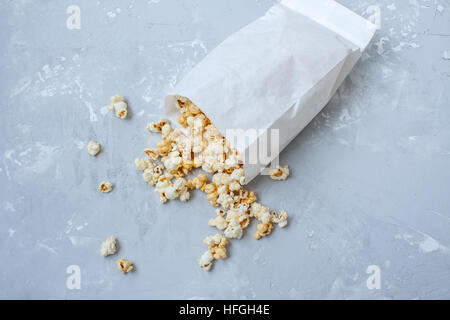 Sweet caramel popcorn in a paper bag on the concrete gray background. - Stock Photo