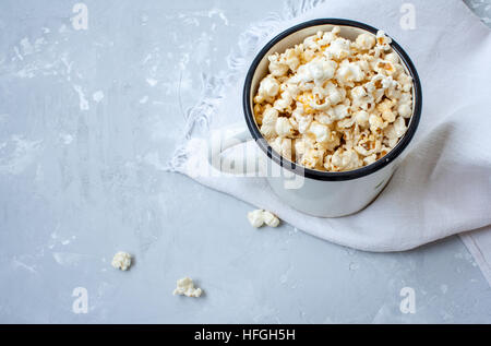 Sweet caramel popcorn in a large iron circle on the concrete gray background. - Stock Photo