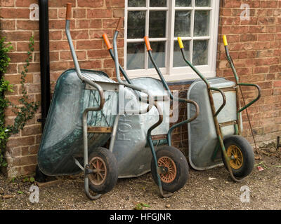 Row of three metal garden wheel barrows leaning against old red brick wall, UK. - Stock Photo