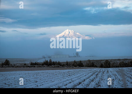 Snowy mountain in clouds with a farm field in foreground which is lightly covered in snow - Stock Photo