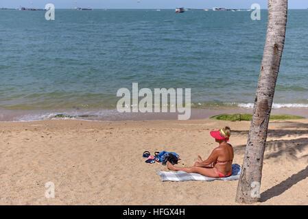 Bikini clad female sunbathing on a tropical beach. Pattaya Thailand S. E. Asia - Stock Photo