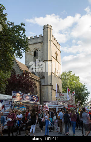St Giles Fair in Oxford with people walking past stall selling a wide variety of food with the tower of St Michael's - Stock Photo