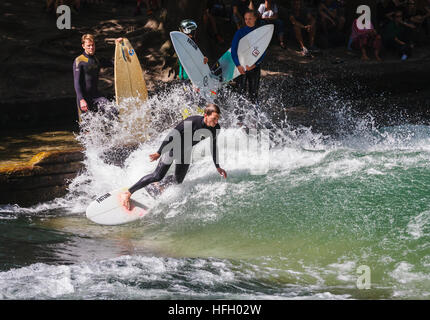 Surfer makes a on the artificial standing wave in the Eisbach in the Munich Englisher Garten, Germany. - Stock Photo