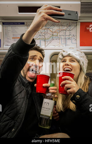 London, UK. 1st January, 2017. New Year's Eve: A merry couple take a selfie photo on the underground Jubilee line - Stock Photo
