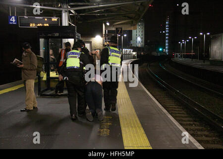 London, UK. 1st January 2017. A drunken man is dragged by police officers at Vauxhall station during the New Years - Stock Photo
