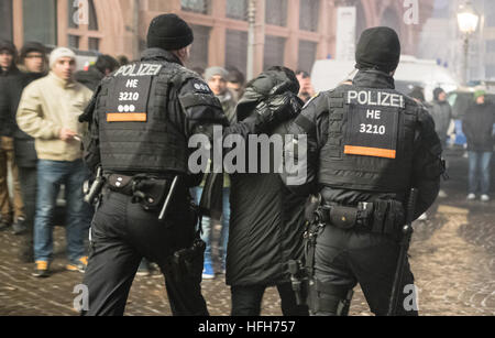 Police officers take a man away on the Roemerberg in Frankfurt am Main, Germany, 31 December 2016. This year a large - Stock Photo