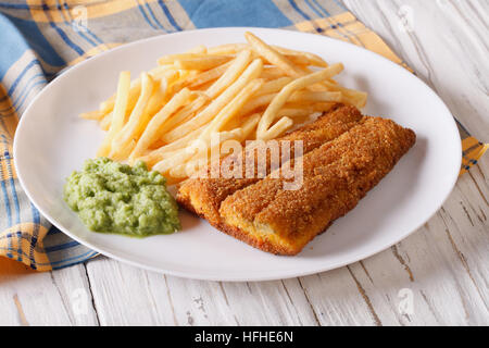 English food: fish in breadcrumbs with fried potatoes and pea puree on a plate. horizontal - Stock Photo
