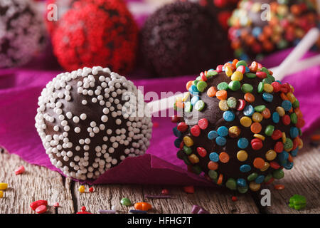 Chocolate cake pops with candy sprinkles macro on an old table. Horizontal - Stock Photo