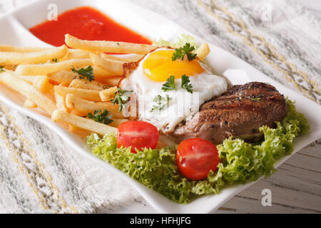 Traditional lunch: a juicy steak, fried egg and French fries on a plate close-up. horizontal - Stock Photo