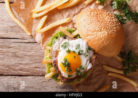 sandwich with grilled meat, a fried egg and French fries. horizontal view from above - Stock Photo