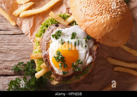 sandwich with grilled meat, a fried egg and French fries close-up. horizontal view from above - Stock Photo