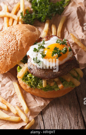Rustic sandwich with beefsteak, fried egg and French fries. vertical - Stock Photo