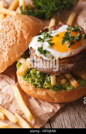 Rustic sandwich with beefsteak, fried egg and French fries close-up. vertical - Stock Photo