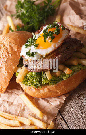 Homemade sandwich with beefsteak, fried egg and French fries close-up. vertical - Stock Photo
