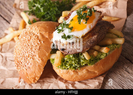 Sandwich with beefsteak, fried egg and French fries close-up. Horizontal - Stock Photo