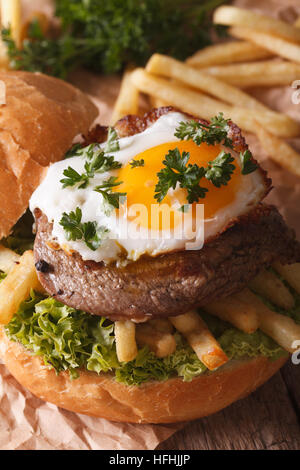 Sandwich with beefsteak, fried egg and French fries close-up. vertical - Stock Photo