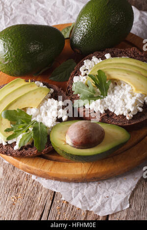 Homemade sandwiches with avocado, cream cheese and arugula close-up. vertical - Stock Photo