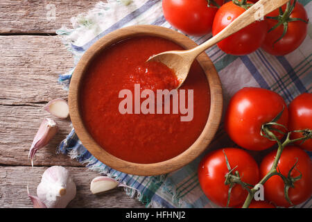tomato sauce with garlic and basil in a wooden bowl closeup. horizontal view from above - Stock Photo