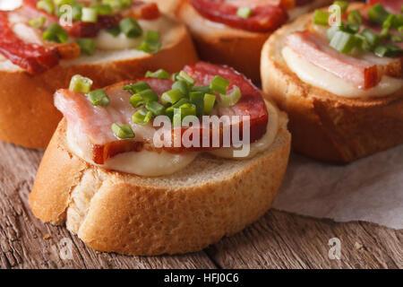 Crostini sandwiches with bacon and mozzarella cheese macro on the table. horizontal - Stock Photo