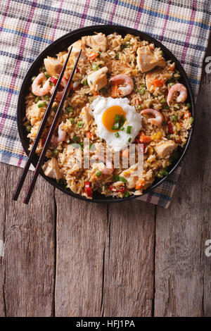 Asian fried rice nasi goreng with chicken, prawns, egg and vegetables vertical view from above - Stock Photo