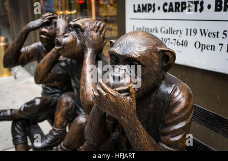 Bronze sculpture of three chimpanzees or monkeys on a bench: 'See, speak, hear no evil' - Stock Photo