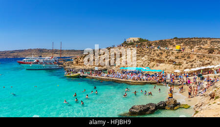 Panoramic view of the Blue Lagoon in Comino island of Malta, with tourists arriving from cruise boats and beach - Stock Photo