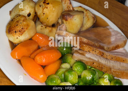 Plate of Roast Pork with fresh vegetables and roast potatoes - Stock Photo